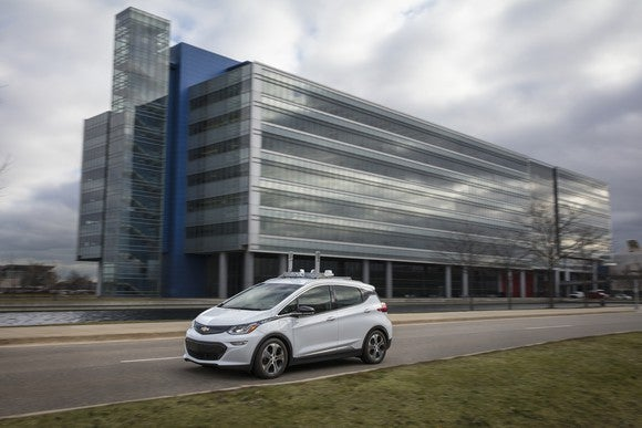 A white Chevrolet Bolt EV with self-driving sensors is shown on a public road near GM's technical center.