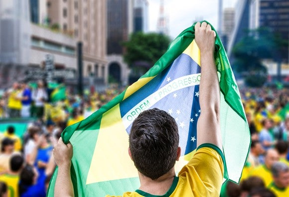 Man in Brazilian green and gold, holding the Brazilian flag