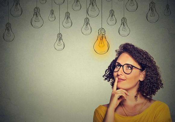 Woman with idea below drawings of light bulbs
