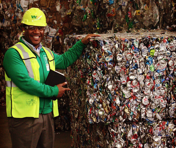 Waste Management employee standing near a large amount of recycled materials and smiling