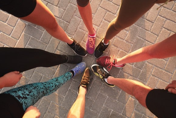 A group of runners' feet meeting in the center of a circle
