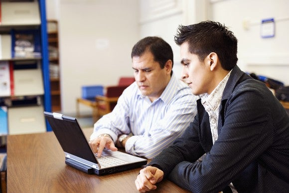 Two adults studying at a computer.