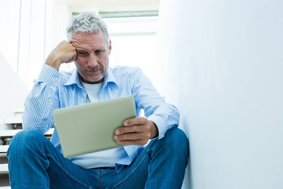 An older man with a worried expression looks at a tablet.