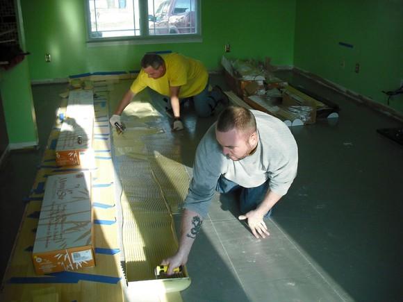 Two Lumber Liquidators installers preparing a floor for laminate flooring.