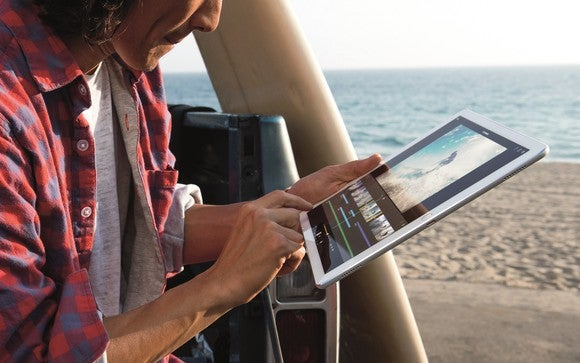A person uses an iPad Pro on the beach.