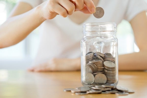 Women's hands putting coins in a jar.