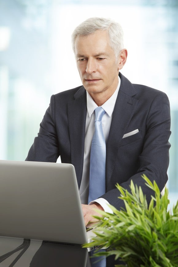 Professional man in a suit and tie on a laptop.