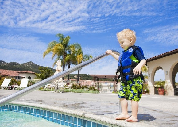 A child stands at the edge of a pool.
