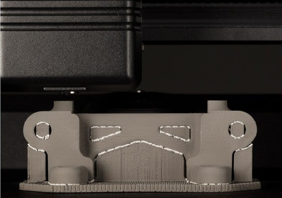 Close-up of a Desktop Metal 3D printer printing a metal part.