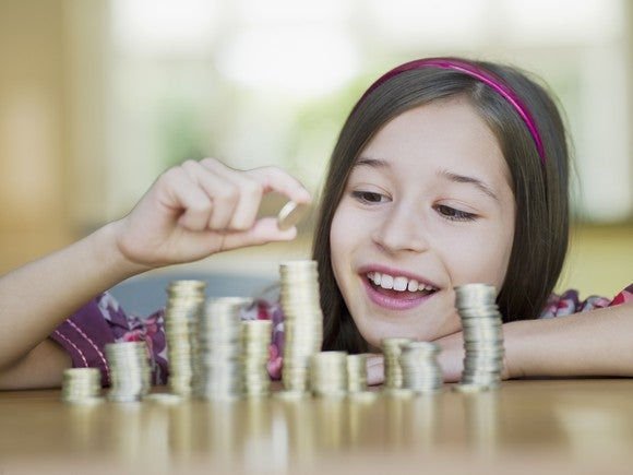 A smiling young girl prepares to place a coin on one of several stacks in front of her.
