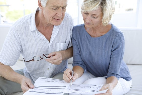 An older husband and wife going over paperwork.