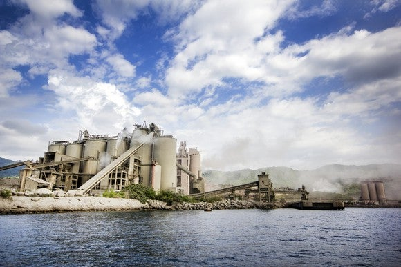 Cement plant at shoreline with blue sky and clouds.