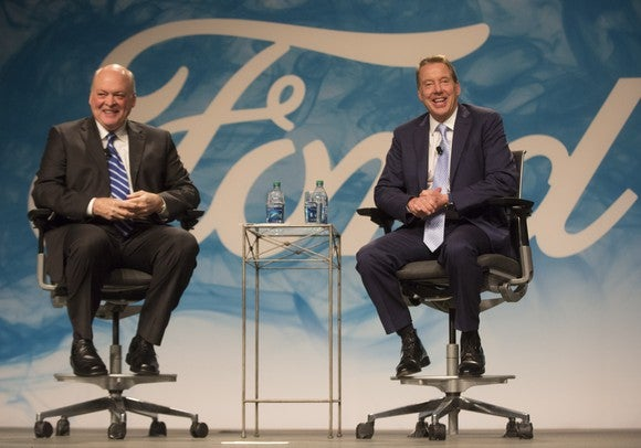 Hackett and Ford are seated on a stage in front of a backdrop of the Ford logo.