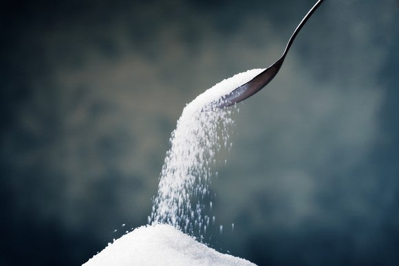 A spoon dumping sweetener onto a pile.