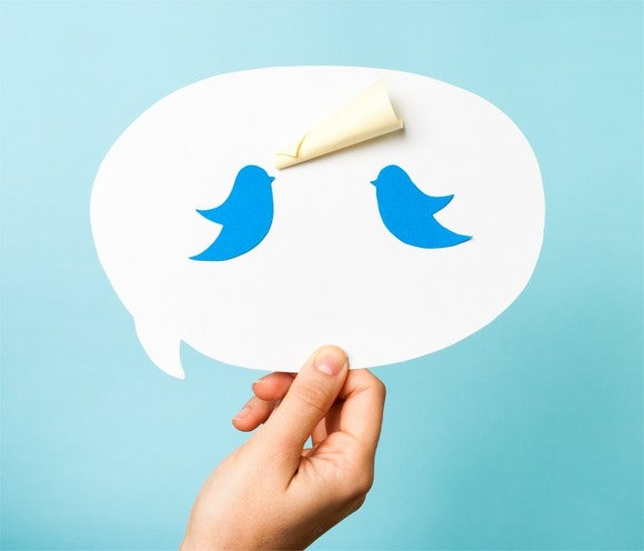 A speech bubble with two Twitter bluebirds tweeting.