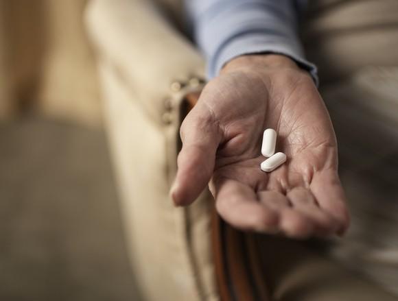 Hand holding 2 pills.