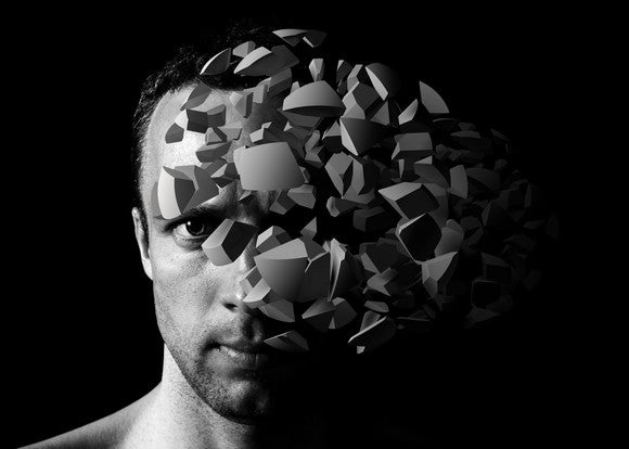 A man with fragments of an object in front of his face.