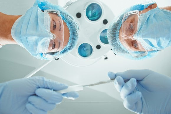 A nurse passes a scalpel to a surgeon, from the perspective of someone lying on an operating table.