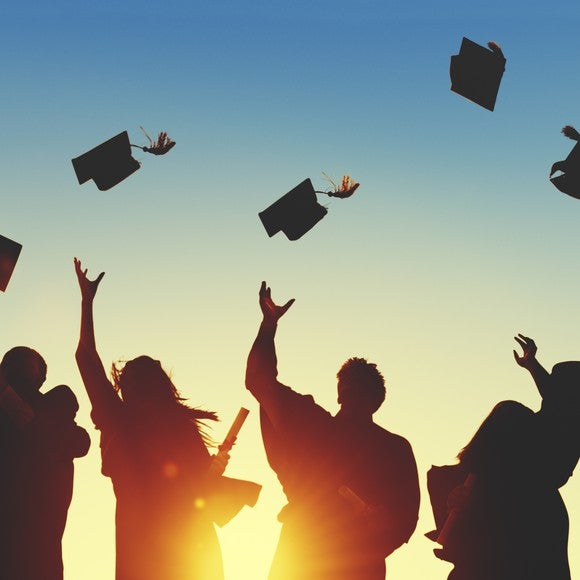Graduates throw their mortarboards in the air.