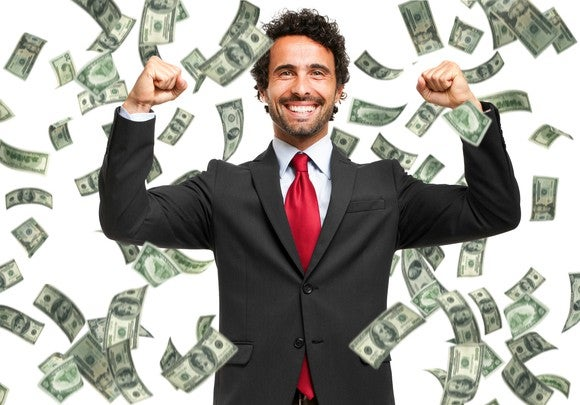 A smiling man in a suit raises his fists in celebration as money falls all around him.