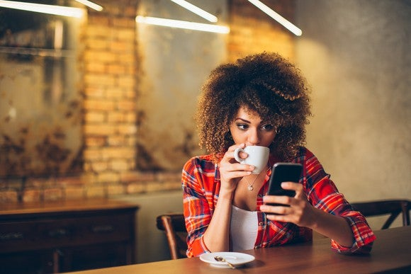 A young woman drinks coffee while checking her messages.