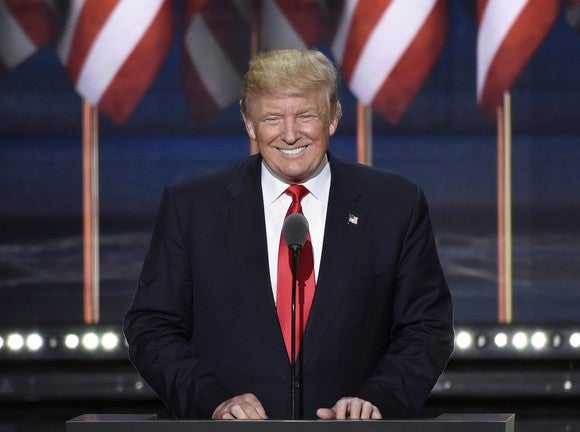 President Donald Trump smiling at podium.
