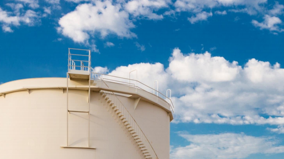 An oil storage tank and blue sky in the background.