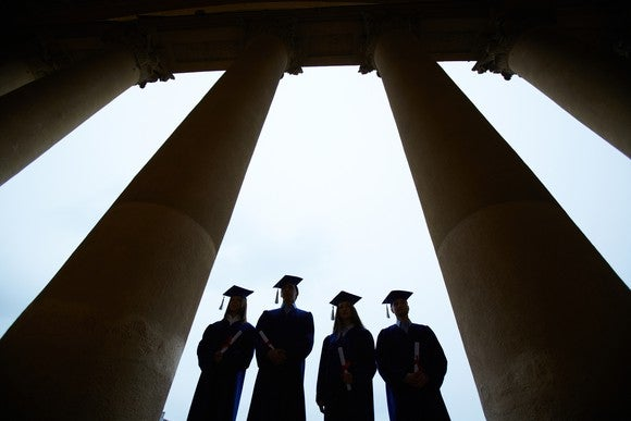 College graduates standing between columns
