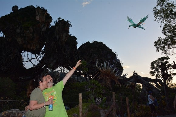 Two people at Disney's Animal Kingdom pointing at a digitally inserted banshee.