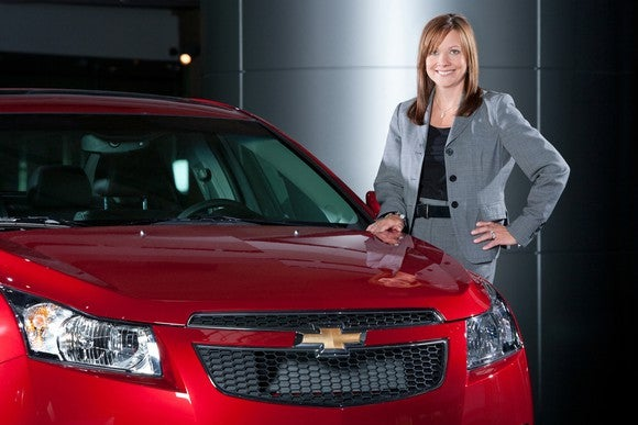 GM CEO Mary Barra next to a GM car.