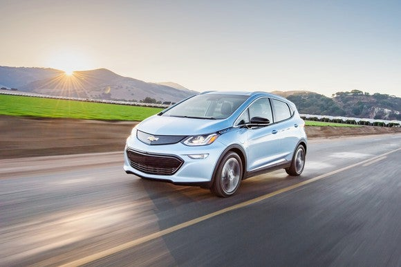 A Chevy Bolt, moving down an open road.