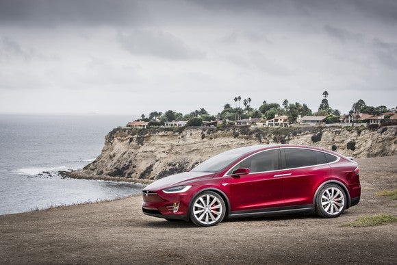 A red Tesla Model X SUV parked on a waterfront.