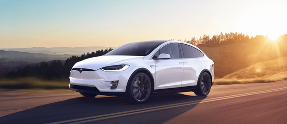 Tesla Model X speeding out of a sunset.