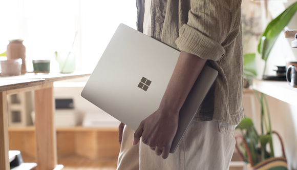 Man holding a Surface laptop.