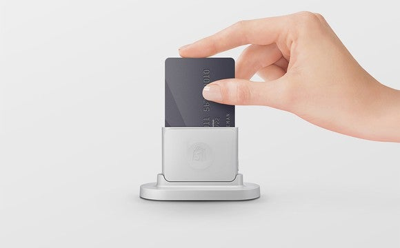 A hand pushing a credit card into Shopify's credit-card chip reader.