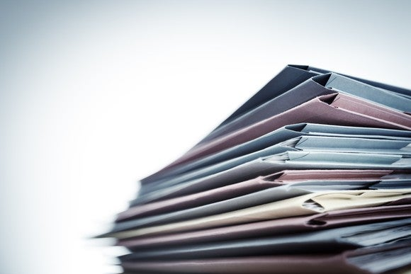 Stack of file folders filled with records.