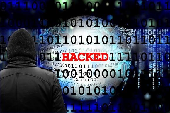 """Binär-Code mit dem Wort """"Hacked"""" über die Mitte."""