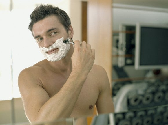 A man shaving in a mirror.
