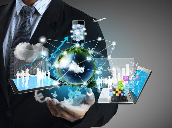 Man in suit with images of a flurry of cloud computing concepts in his hand.