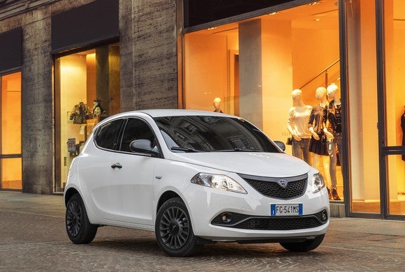 A white Lancia Ypsilon hatchback on a city street.