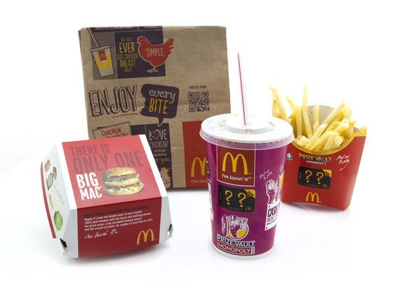 A McDonald's bag, hamburger container, fries, and soft drink.