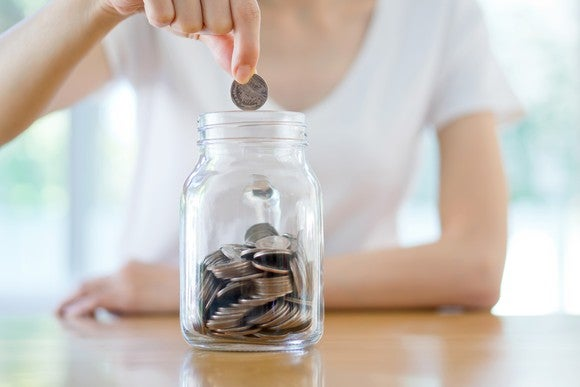 Woman placing coins in a jar.
