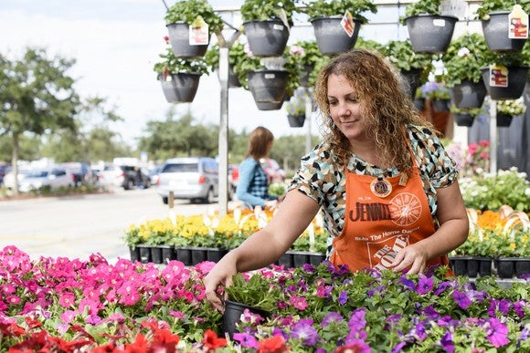 A Home Depot associate tends to a display of flowers.