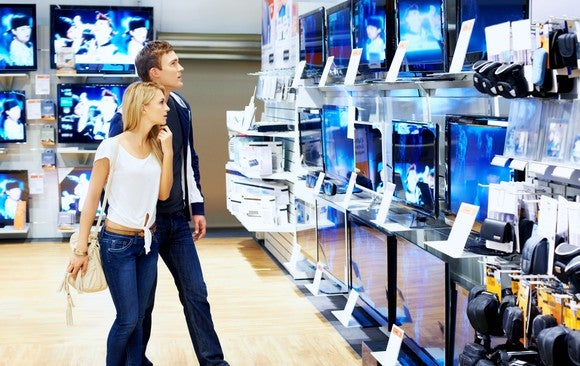 A couple looks at TVs in a retail store.
