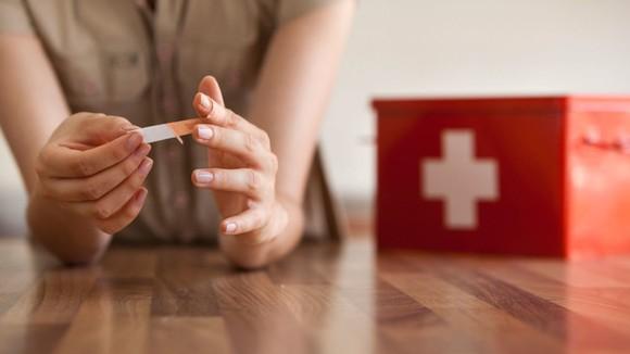 Woman applying a Band-Aid brand bandage
