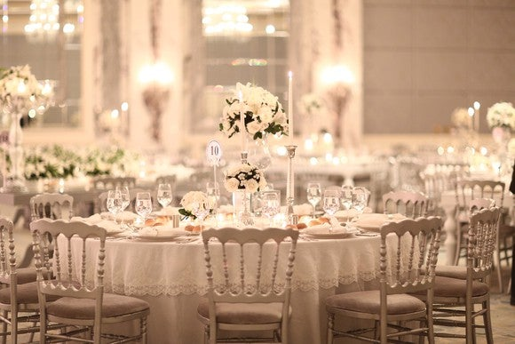 Luxurious white wedding reception tables with candles and floral centerpieces