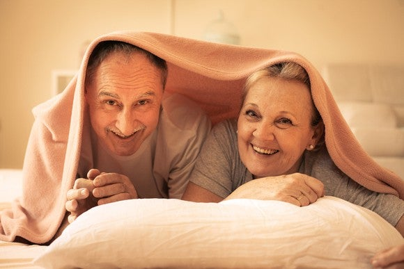 An elderly couple peeking out from underneath their sheets.