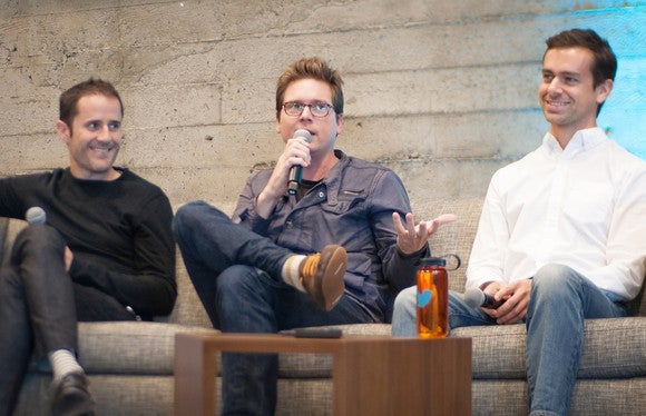 Twitter co-founders seated on couches, talking.