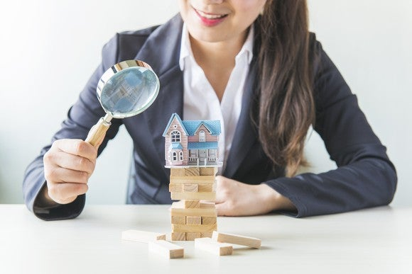 A woman looks through a magnifying glass at a model house piled on a stack of blocks.