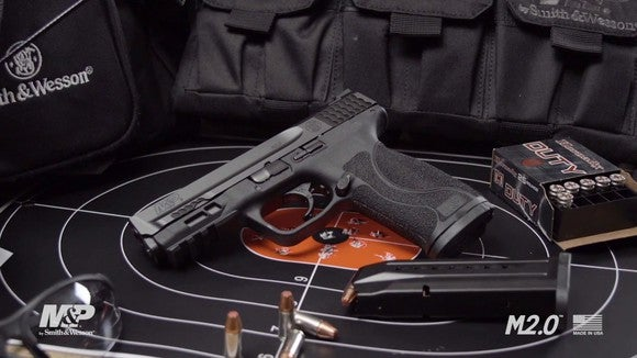 A Smith & Wesson M&P 2.0 handgun, surrounded by bullets and lying on top of a target.